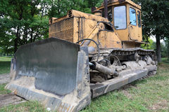 Bulldozer in park. Old bulldozer in park amongst green trees royalty free stock photography