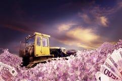 Bulldozer with piles of money Royalty Free Stock Photo