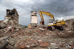 Bulldozer removes the debris from demolition of derelict buildings Stock Photo