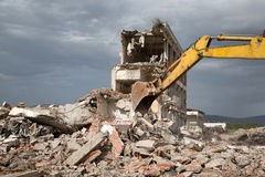Bulldozer removes the debris from demolition of derelict buildings Royalty Free Stock Photography
