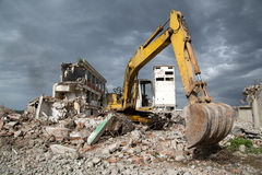 Bulldozer removes the debris from demolition of derelict buildings Royalty Free Stock Images