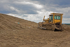 Bulldozer at revitalization of landfill. And the coludy sky Stock Photography