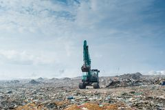 Bulldozer riding at the garbage dump full of smoke, litter, plastic bottles,rubbish and trash at tropical island. Bulldozer riding at the huge garbage dump full Stock Photos