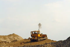 Bulldozer on sand heap Royalty Free Stock Photos