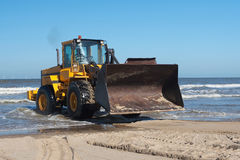 Bulldozer from sea. Action shot of an yellow digger at the coast royalty free stock photo