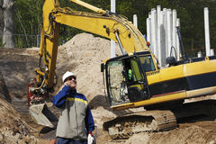 Bulldozer and site worker in action Stock Photography
