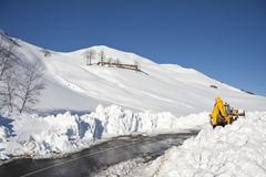 Bulldozer for snow removal. Mountain panorama of the snow in a sunny winter day Royalty Free Stock Photography