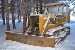 Bulldozer som täckas med den insnöade skogen royaltyfri foto