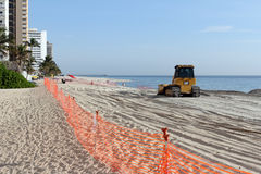 Bulldozer Spreading New Beach Sand. Fort Lauderdale, FL, USA - March 3, 2016: Fenced in beach with a bulldozer replenishing sand in a nourishment project. An Royalty Free Stock Images