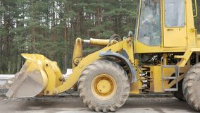 A bulldozer stands on the road. Inside, a worker sleeps at lunchtime stock footage