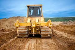 Bulldozer with steel blade moving soil and sand around Royalty Free Stock Images