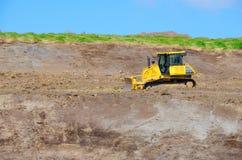 Bulldozer tractor working on steep hillside Stock Photo