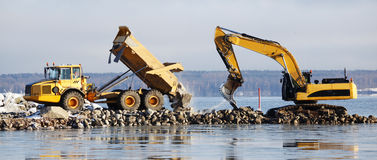 Bulldozer and truck in dredging works Royalty Free Stock Photos