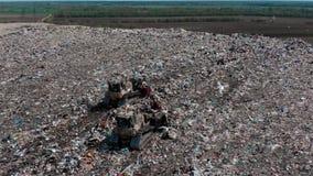 Bulldozer twee die aan berg van huisvuil in stortplaats werken stock videobeelden