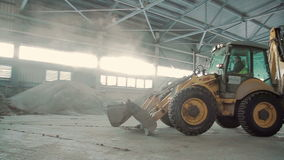 Bulldozer in warehouse. Work with sand stock footage