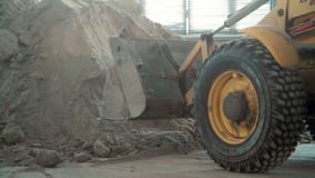 Bulldozer in warehouse. Work with sand stock video footage