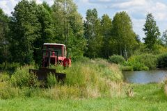 Bulldozer and water. Damaged bulldozer in the area lakes for breeding Stock Photo