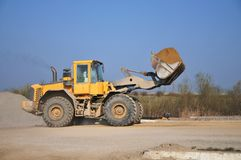 Bulldozer at work. Against the blue sky Stock Photos