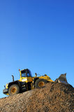 Bulldozer at Work. Yellow bulldozer working on a pile of stone aganist a clear blue sky Royalty Free Stock Images