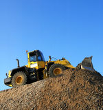 Bulldozer at Work. Yellow bulldozer working on a pile of stone aganist a clear blue sky, square format Stock Photography