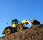 Bulldozer at Work. Yellow bulldozer working on a pile of stone aganist a clear blue sky, square format Royalty Free Stock Photo