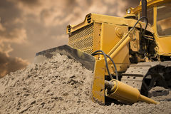 Bulldozer. At work on the orange sky background Royalty Free Stock Photography