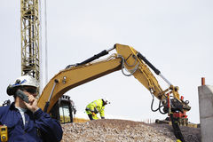 Bulldozer and workers in action Stock Photos