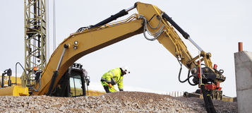 Bulldozer and workers in action Stock Images