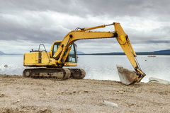 Bulldozer working in a construction site. An excavation machine working in a new road construction Royalty Free Stock Images