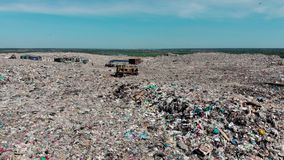 Bulldozer working on mountain of garbage in landfill