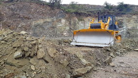 Bulldozer working in a quarry. Bulldozer working with blade in a mine Royalty Free Stock Photo