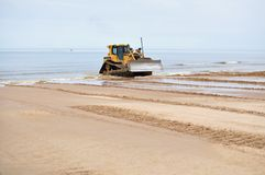 Bulldozer working at seashore Stock Photos