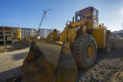 Bulldozergraafwerktuig op een bouwwerf tegen de hemel stock afbeelding
