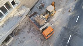 Bulldozerlader die afval en puin uploaden in stortplaatsvrachtwagen bij bouwwerf de bouw het ontmantelen en bouw stock video