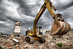 Bulldozern tar bort skräpet från rivning av övergivna byggnader Arkivfoton