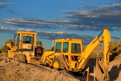 Bulldozers. Two bulldozers working. The bulldozers are in front of a cloudscape Royalty Free Stock Image