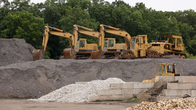 Bulldozers All In A Row. Bulldozers lined up at a construction site with building materials in the foreground Stock Images