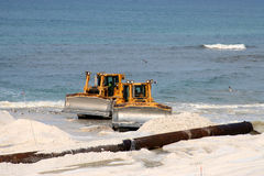 Bulldozers on the beach. Two bulldozers and pipe on a white sandy beach, or a vacation nightmare Royalty Free Stock Images