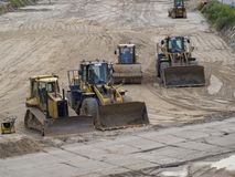 Bulldozrar som väntar på fält efter arbetsdags arkivfoton