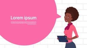 Bulle de causerie de Holding Tablet Speak de femme d'affaires d'afro-américain grande avec l'espace de copie des textes Photo stock