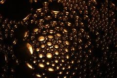 Bulle de l'eau colorée par or Photo stock