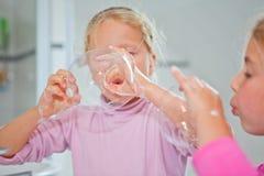 Bulle de savon de soufflement de petite fille image stock