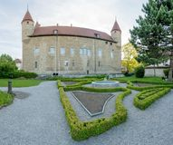 Bulle, FR / Switzerland - 1 June 2019: the gardens and the historic city hall administrative building in the Swiss village of. Bulle in canton Fribourg royalty free stock photos