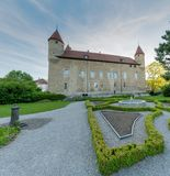 Bulle, FR / Switzerland - 1 June 2019: the gardens and the historic city hall administrative building in the Swiss village of. Bulle in canton Fribourg royalty free stock image