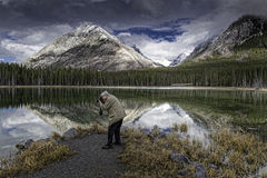 Buller Pond Panoramic. A photographer frames up a reflective image in the stillness of Buller Pond in Alberta Canada's Rockie Mountains Royalty Free Stock Image