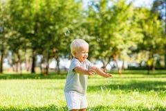 Bulles de savon contagieuses d'enfant heureux dans le jardin photographie stock