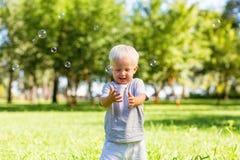 Bulles de savon contagieuses de petit garçon belles dehors images libres de droits