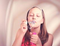 Bulles de savon de soufflement de fille de l'adolescence heureuse Image stock