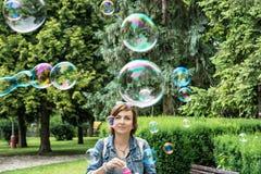 Bulles de savon de soufflement de jeune femme caucasienne en parc de ville Photographie stock