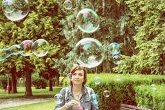 Bulles de savon de soufflement de jeune femme caucasienne en parc de ville, guerre Images stock